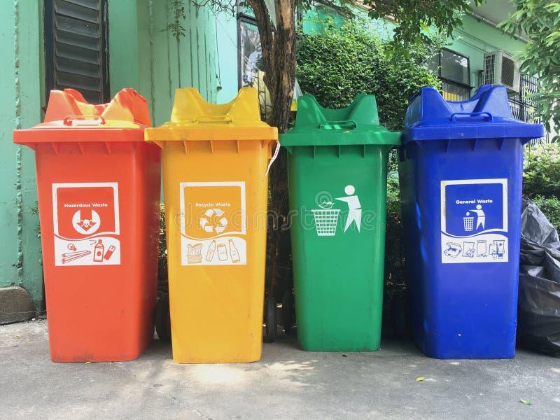 红色黄绿色和蓝色,回收站与在修造回收大方的本体空间和标志室外附近 免版税库存图片