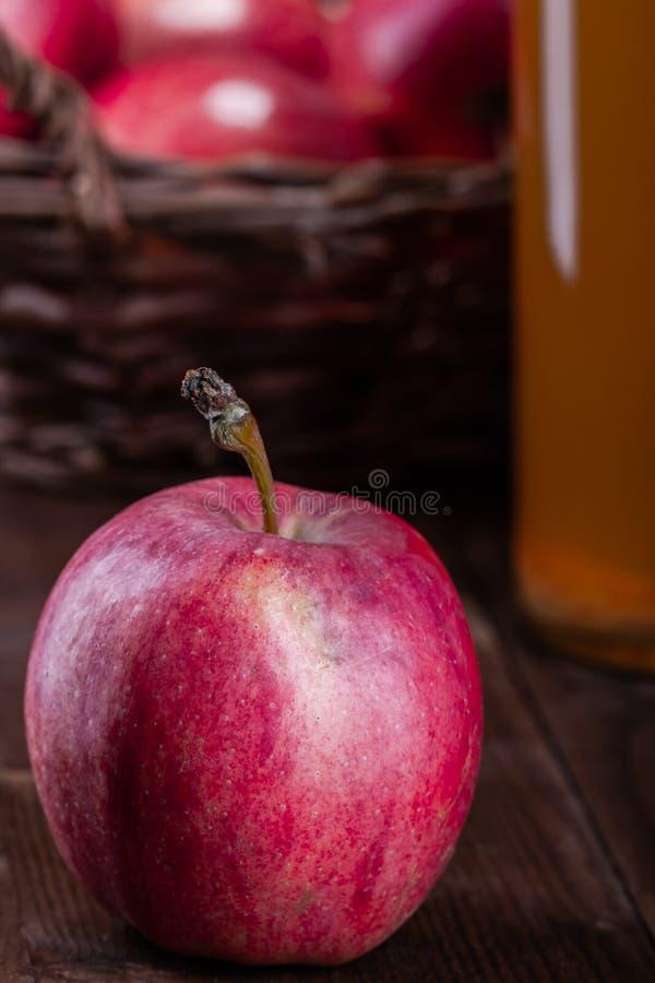 红色,有机苹果 在一个木篮子的果子在一张木桌上 图库摄影