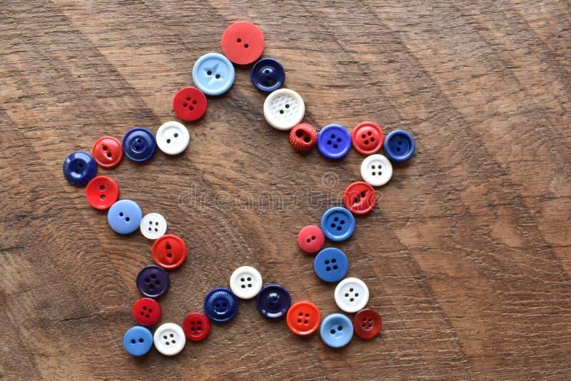 红色,白色和蓝色缝合的按钮星形状 免版税库存照片