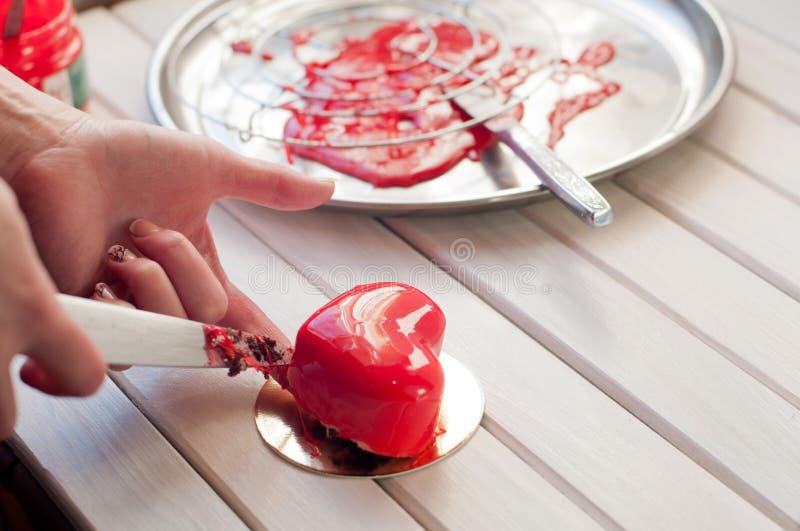 红色给上釉的心形的蛋糕和金属盘子 穿着糖果店 库存照片