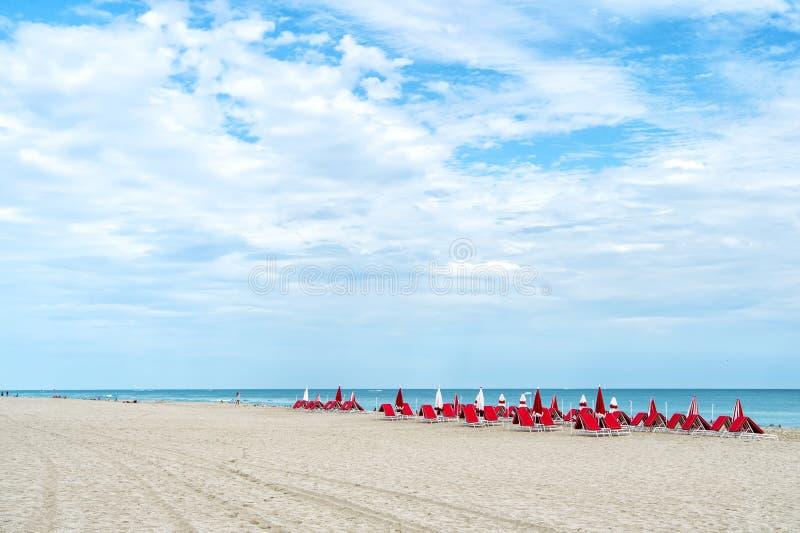 红色轻便折叠躺椅,在海岸,南海滩,迈阿密,佛罗里达的伞 免版税库存图片