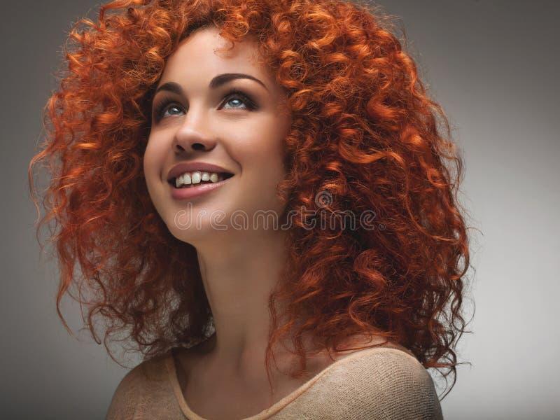 红色头发。有卷曲长的头发的美丽的妇女。优质ima 图库摄影
