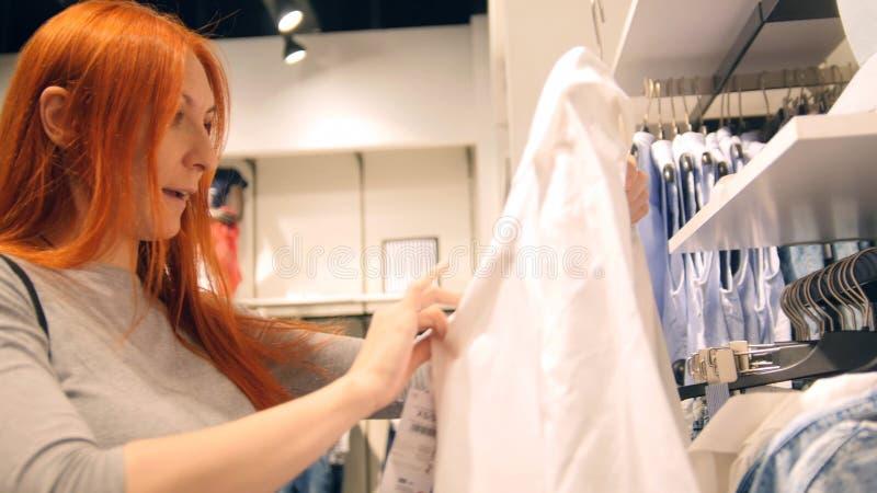 红色头发妇女选择在妇女` s服装店的一件礼服 免版税库存图片