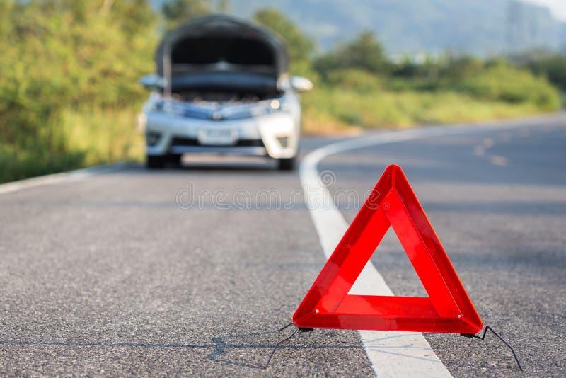 红色紧急刹车标志和残破的汽车在路 免版税库存图片
