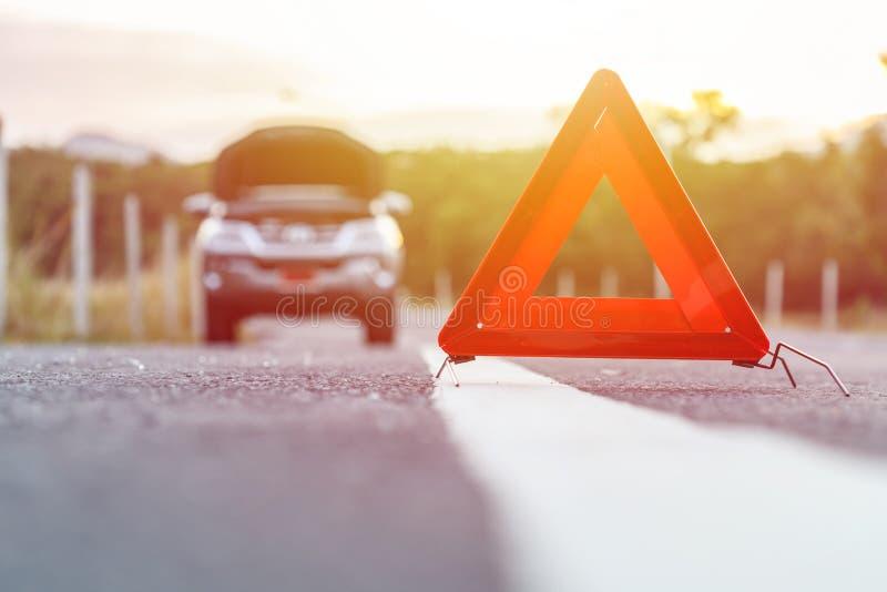 红色紧急刹车标志和残破的银色汽车在路 免版税库存图片