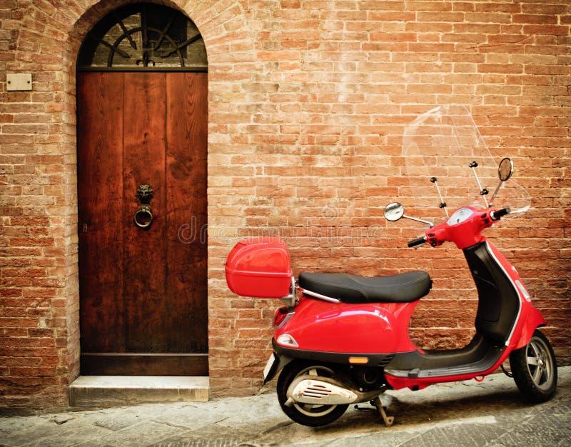 红色滑行车的葡萄酒图象在街道上的 免版税库存照片