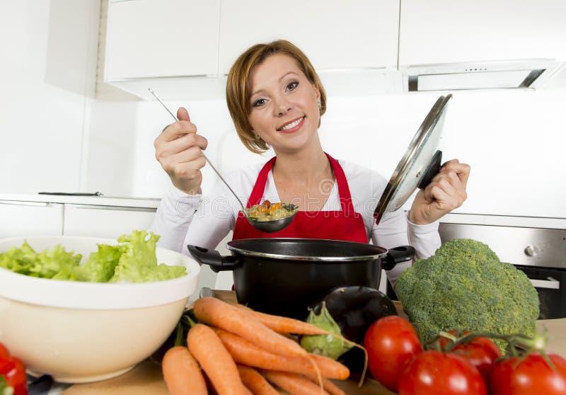 红色围裙的年轻愉快的家庭厨师妇女在拿着平底深锅的国内厨房品尝热的汤 免版税库存图片