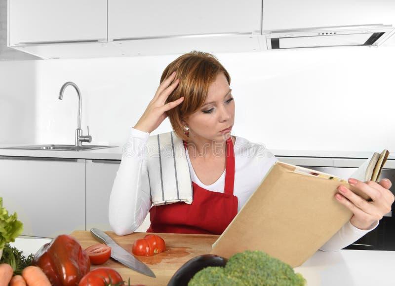 红色围裙的年轻美丽的家庭厨师妇女在现代国内厨房读书菜谱在食谱后 库存图片