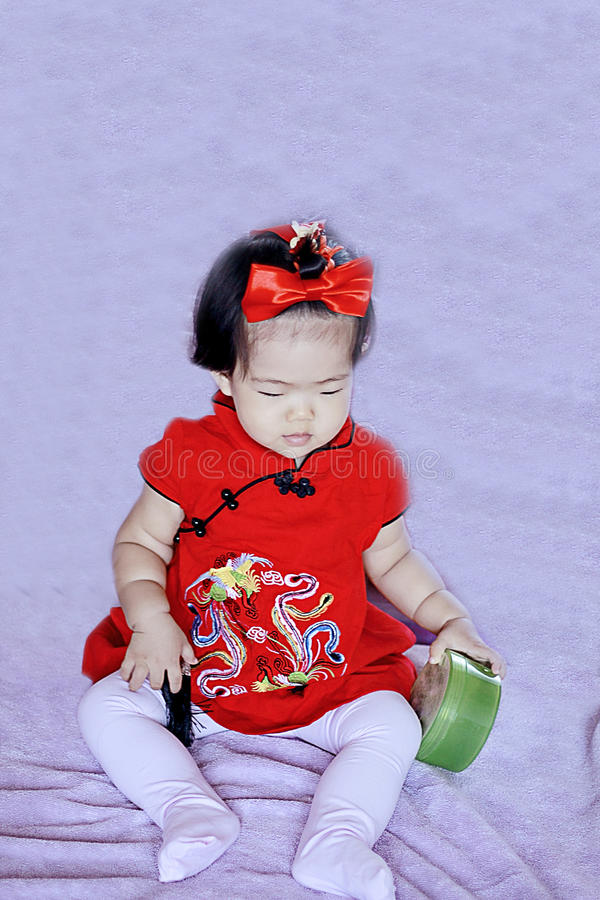 红色cheongsam的逗人喜爱的中国矮小的婴孩获得乐趣 免版税库存照片