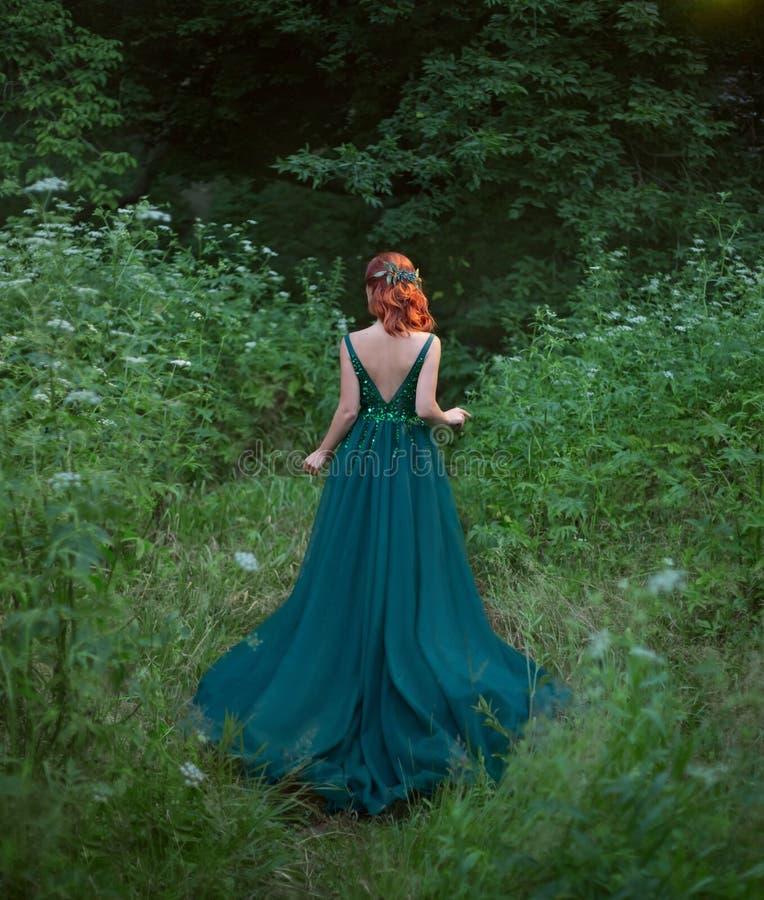 红色hait女孩去站立与悦目的森林回到照相机 库存照片