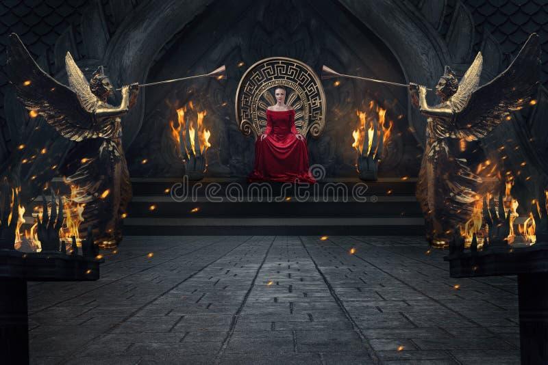 红色luxuious礼服的庄严妇女坐在皇家内部的王位 免版税库存照片