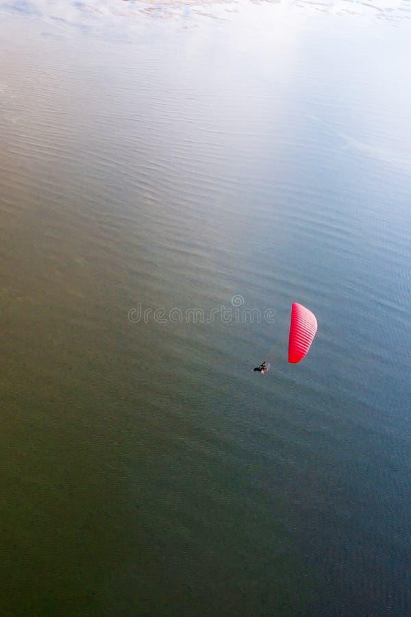 红色paramotor飞行顶视图在含沙的在热带海 免版税图库摄影