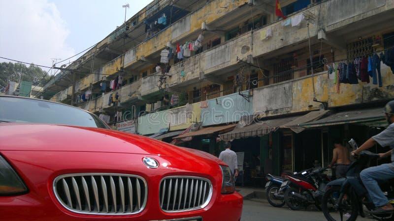 红色rodster汽车在越南贫民窟 免版税库存照片