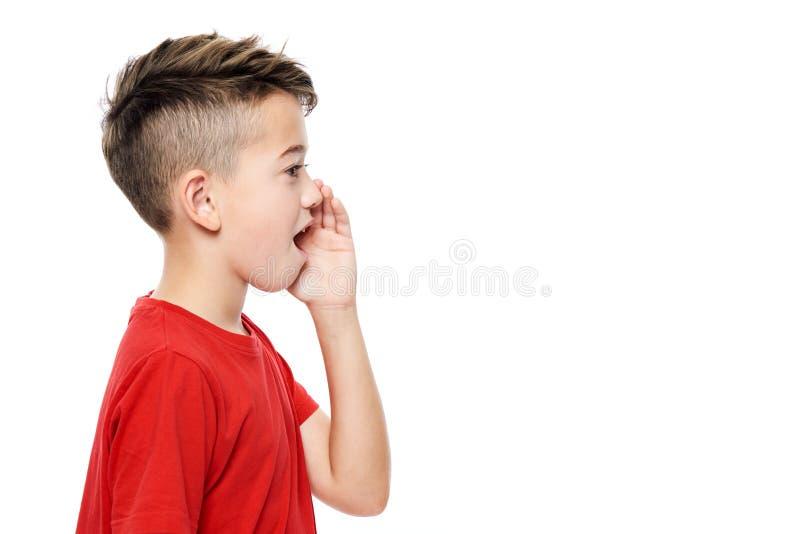 红色T恤杉呼喊的逗人喜爱的男孩 在白色背景的语言矫正概念 侧视图 库存照片