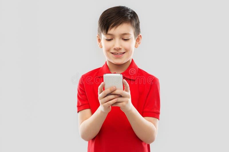 红色T恤杉的微笑的小男孩使用智能手机 免版税库存照片