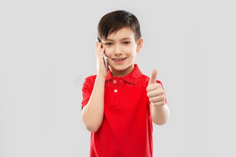 红色T恤杉的微笑的男孩拜访智能手机的 免版税库存照片