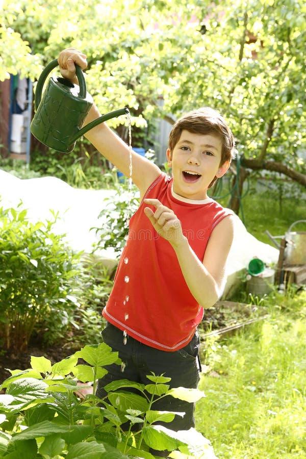 红色T恤杉的男孩有喷壶的 免版税库存照片