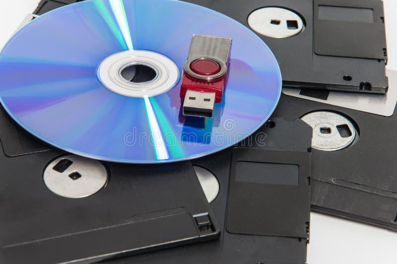红色usb驱动被投入的cd和有disket在他们下 免版税库存图片