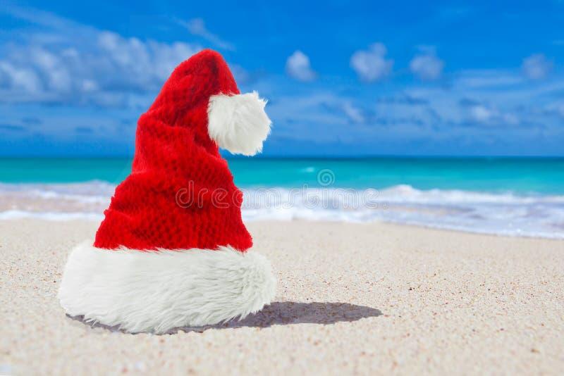 红色Xmas或圣诞节圣诞老人帽子天堂海滩 库存照片