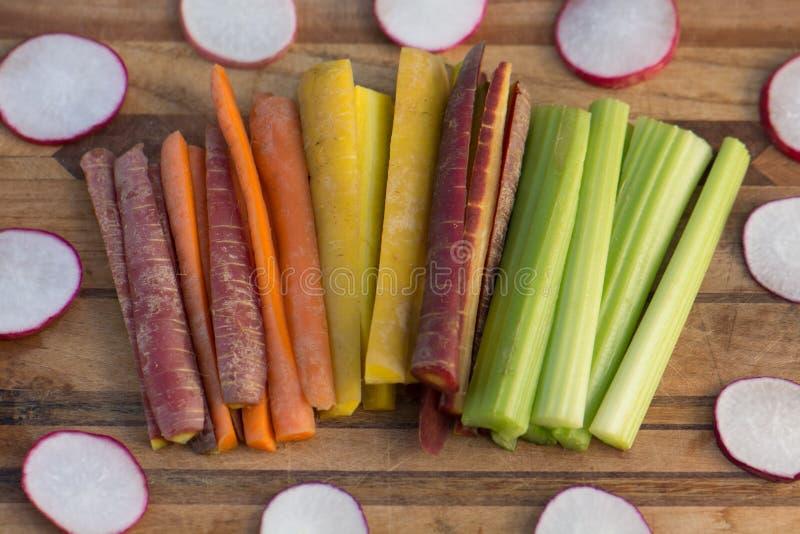 红萝卜、萝卜和芹菜在一个木切板 库存图片