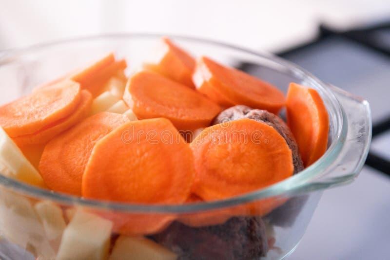 红萝卜切片圆n在玻璃平底锅的火炉,准备汤 库存图片