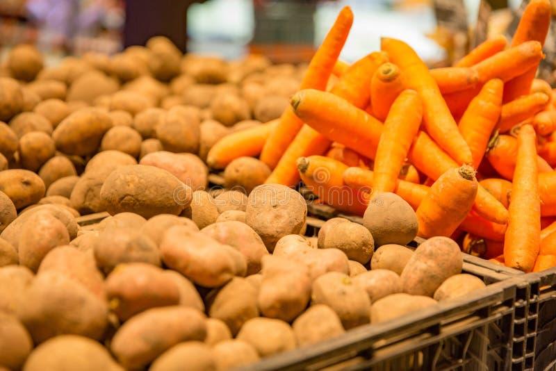 红萝卜和土豆在篮子在农夫市场上 免版税库存照片