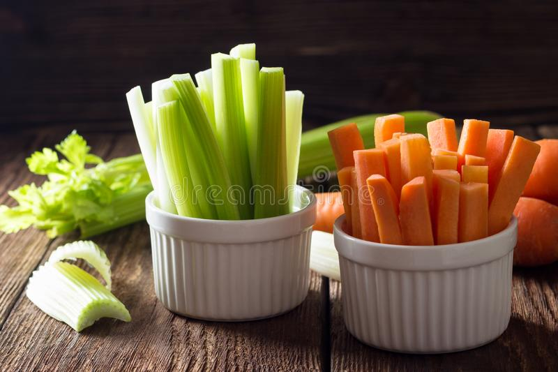 红萝卜和芹菜棍子在白色碗 免版税库存照片