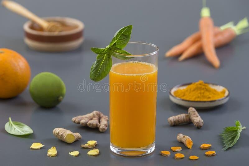 红萝卜姜免疫促进,反激动的圆滑的人用姜黄和蜂蜜 戒毒所早晨汁液饮料, 库存照片