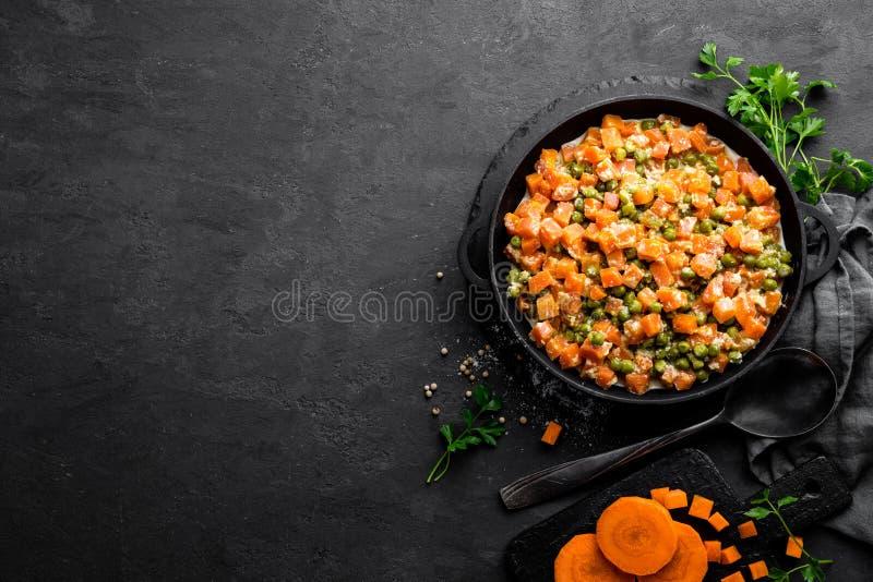红萝卜炖用在乳脂状的牛奶调味汁在stewpan,菜的新鲜的绿豆在黑背景嫩煎 库存图片