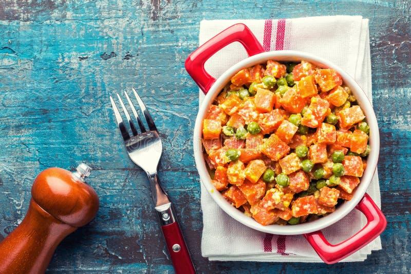 红萝卜炖用在乳脂状的牛奶调味汁的新鲜的绿豆在stewpan 免版税库存图片