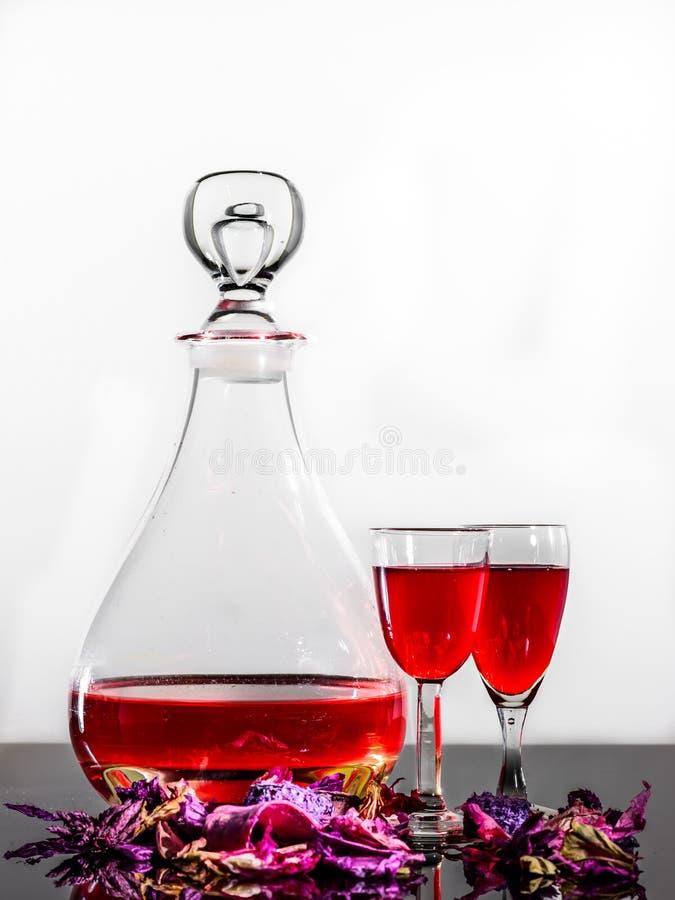 红葡萄酒、一个酒壶、两个酒杯, &有些瓣反射性表面上 免版税库存图片