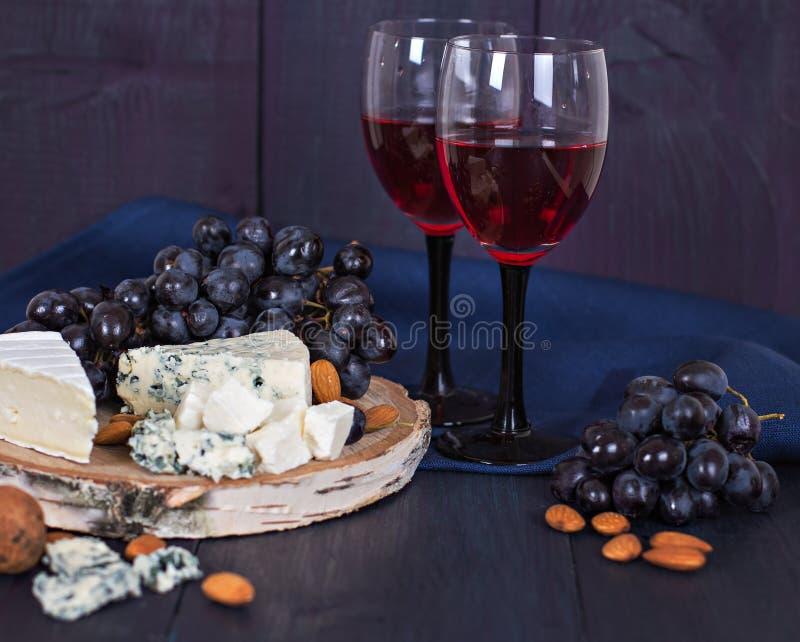 红葡萄酒和快餐 酒,葡萄,乳酪,坚果,橄榄 浪漫晚上,静物画 免版税库存图片