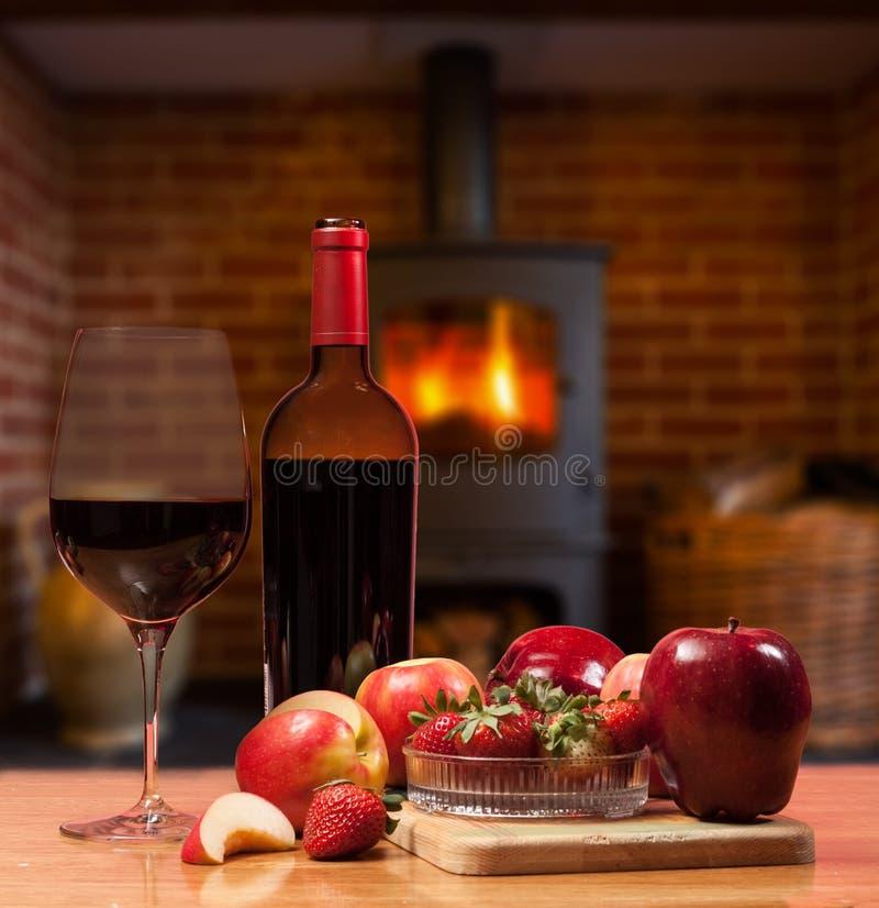红葡萄酒和果子在灼烧的火前面 免版税图库摄影