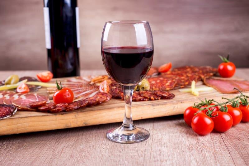 红葡萄酒和熏制的肉熟食 免版税库存照片