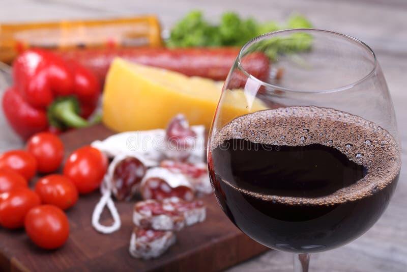 红葡萄酒在玻璃和食物背景中 库存照片