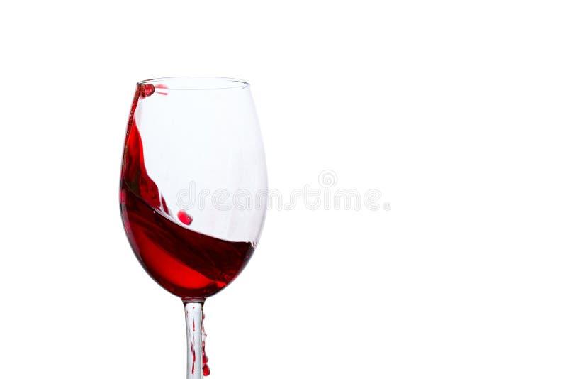 红葡萄酒明亮的飞溅在玻璃边缘的 库存照片