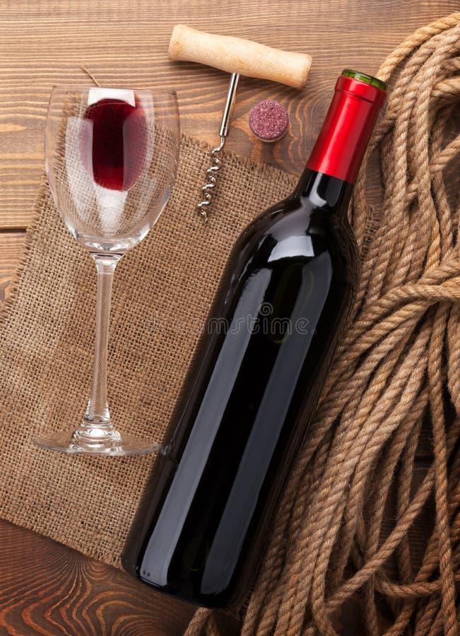 红葡萄酒瓶、玻璃、黄柏和拔塞螺旋 在视图之上 免版税库存照片