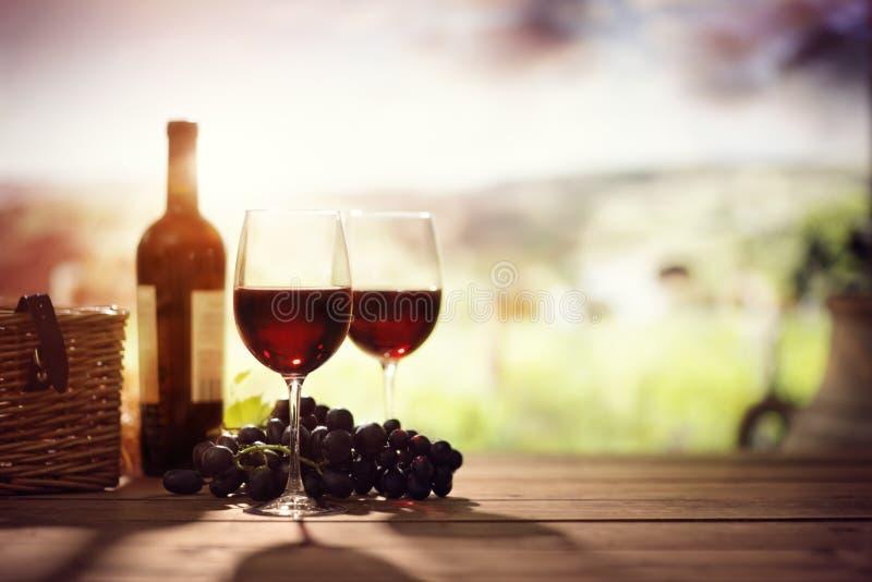 红葡萄酒瓶和玻璃在桌上在葡萄园托斯卡纳意大利里 库存照片