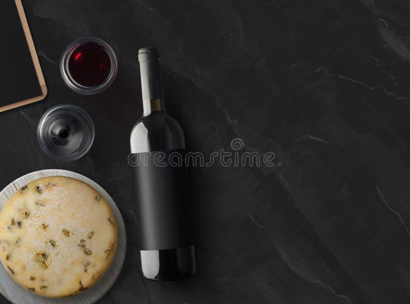 红葡萄酒瓶用乳酪和葡萄酒杯在黑石背景与拷贝空间 免版税图库摄影