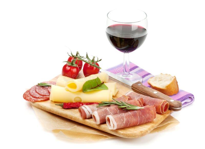 红葡萄酒用乳酪、熏火腿、面包、菜和香料 图库摄影