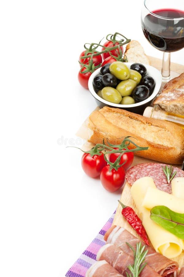 红葡萄酒用乳酪、熏火腿、面包、菜和香料 免版税库存图片