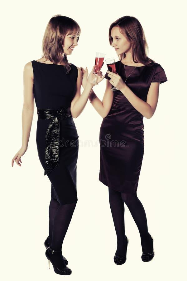 戴红葡萄酒眼镜的两名年轻时尚妇女 库存图片