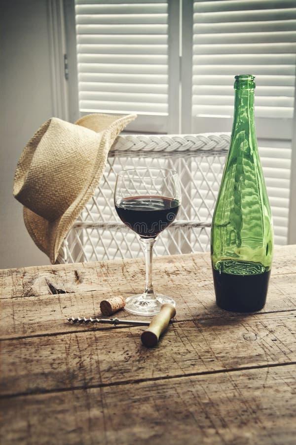 红葡萄酒站立在与草帽的桌上的杯 免版税库存照片
