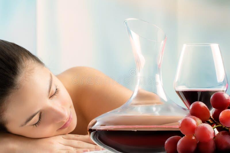 红葡萄酒蒸馏瓶和葡萄与妇女在背景中 免版税库存照片