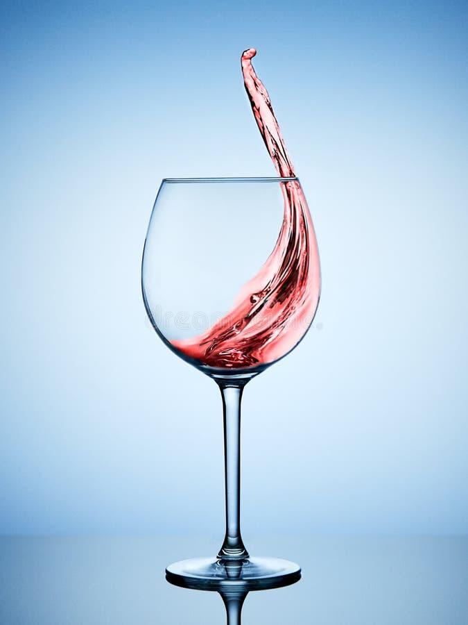 红葡萄酒飞溅在玻璃的 免版税图库摄影