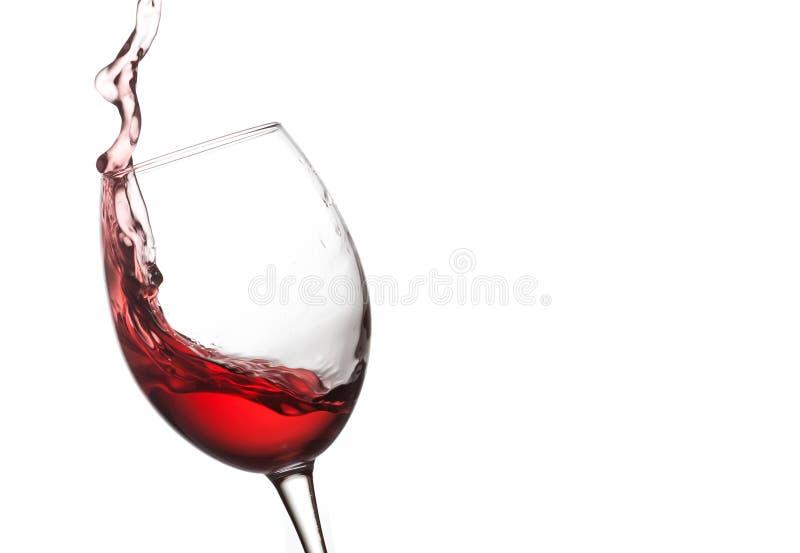 红葡萄酒飞溅 倾吐的酒到水晶玻璃,特写镜头,白色背景里 复制空间 免版税图库摄影