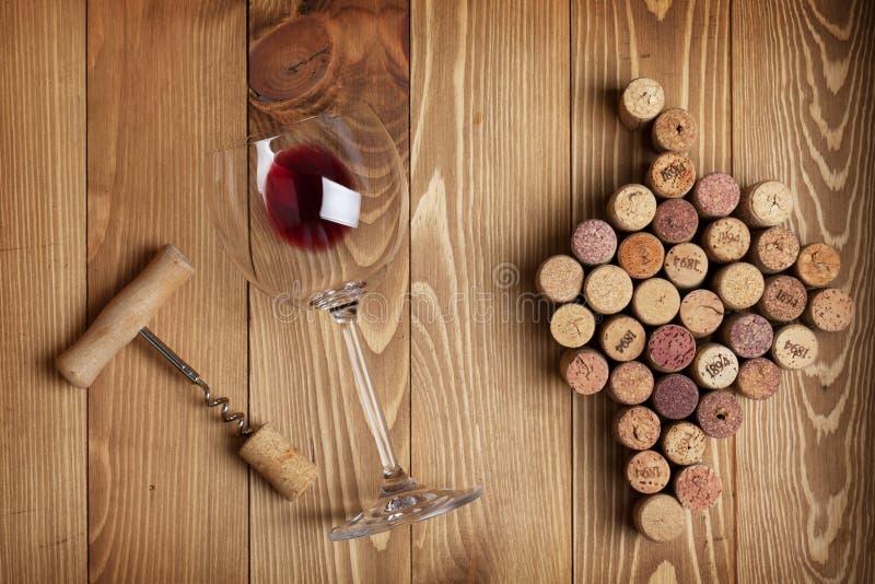 红葡萄酒玻璃、拔塞螺旋和葡萄塑造了黄柏 库存图片