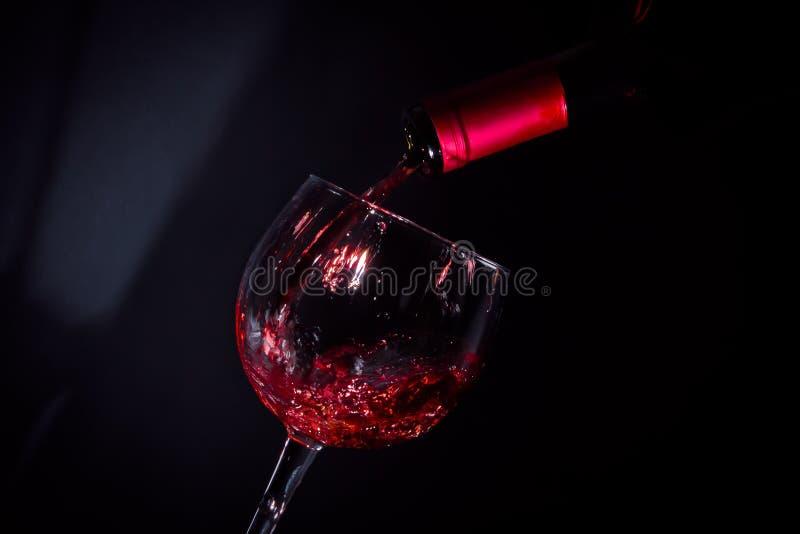 红葡萄酒玻璃在窗口附近的阴影填装了 免版税库存图片