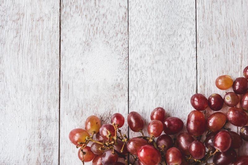 红葡萄顶视图在白色木桌背景的 库存照片