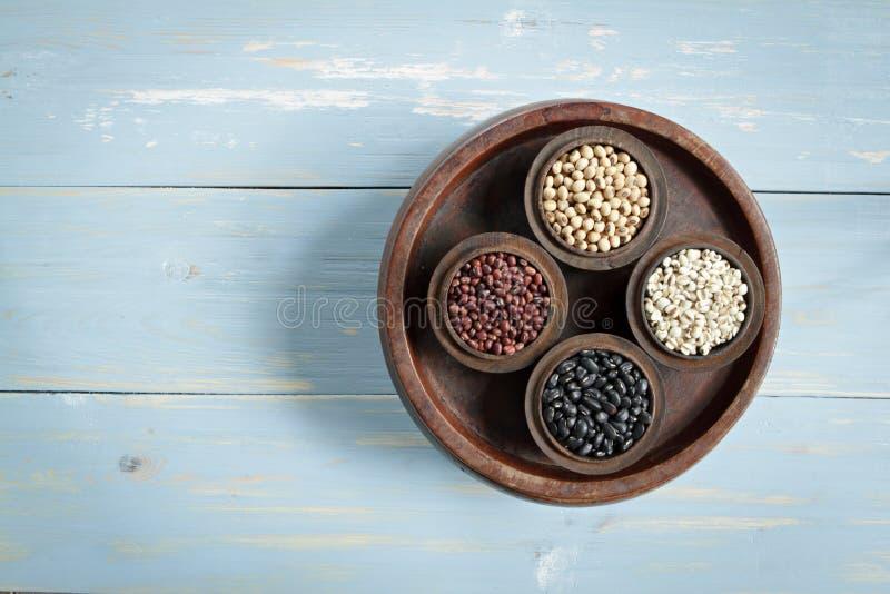 红豆、黑豆、小米和黑眼豆在木碗在木背景设置了 库存图片